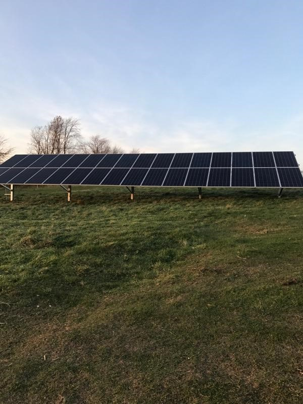 Photo of residential ground mounted solar array in open field
