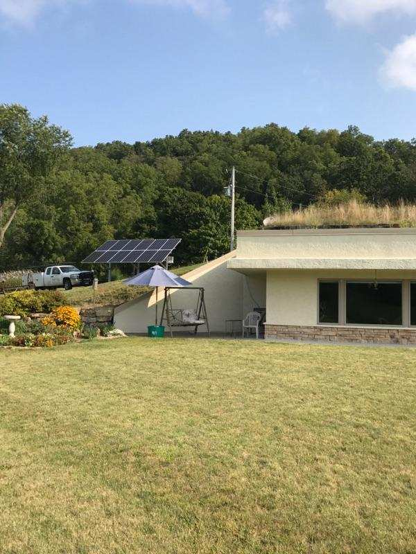 Photo of residential ground mounted solar array behind side of house