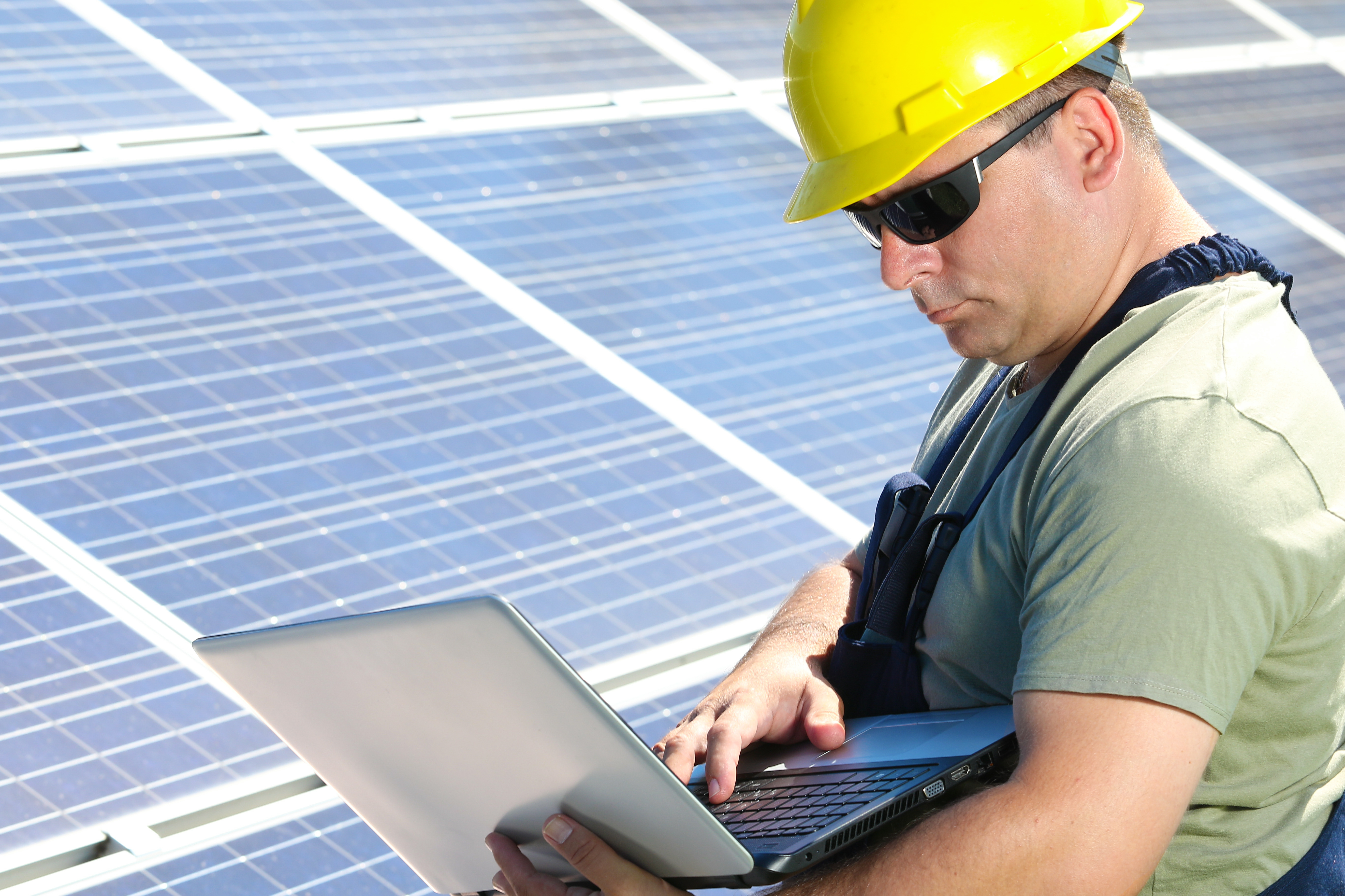 Photo of Green energy power plant and engineer with laptop