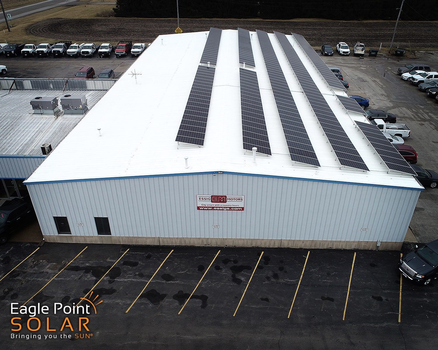 Side view photo of commercial roof mounted solar array on Essig Motors