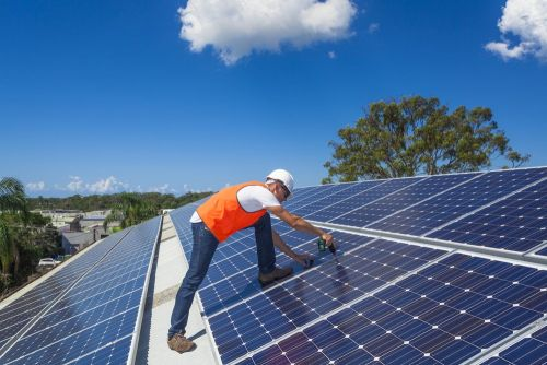 Photo of construction worker installing roof top solar