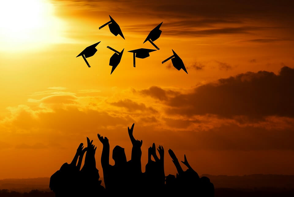 Photo of graduates silhouettes throwing caps in the air