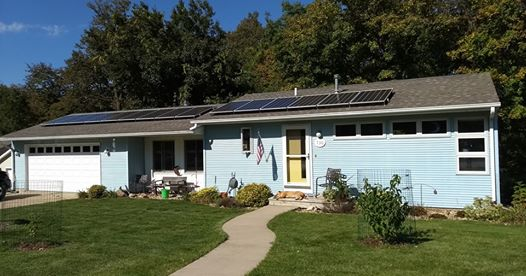 Blue ranch-style house with Eagle Point Solar panels mounted on the roof.