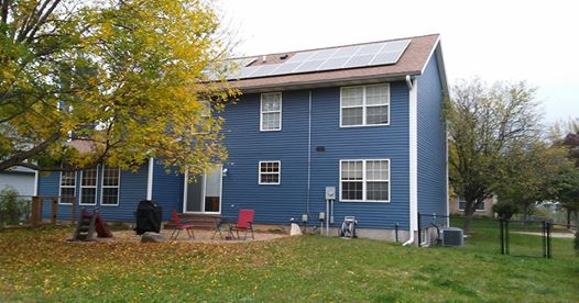 Photo of a roof solar array on a two story blue house