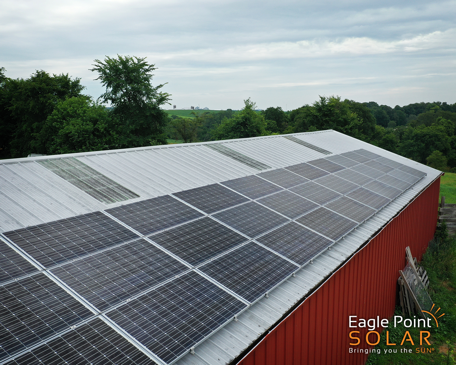 Close up arial photo of roof mounted solar array on small farm shed.